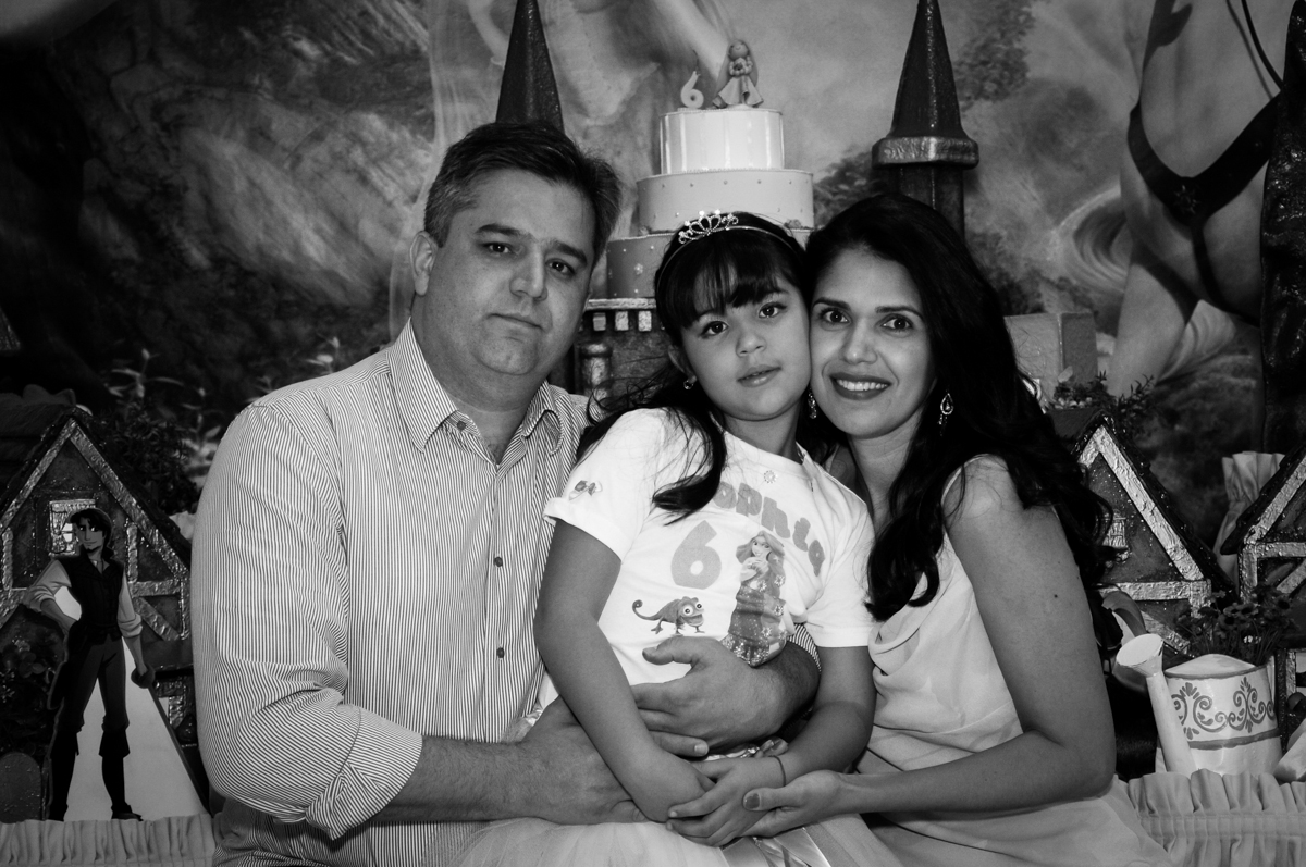 foto dos pais com a aniversariante em frente a mesa tema rapunzel no Buffet Fábrica da Alegria Osasco, São Paulo