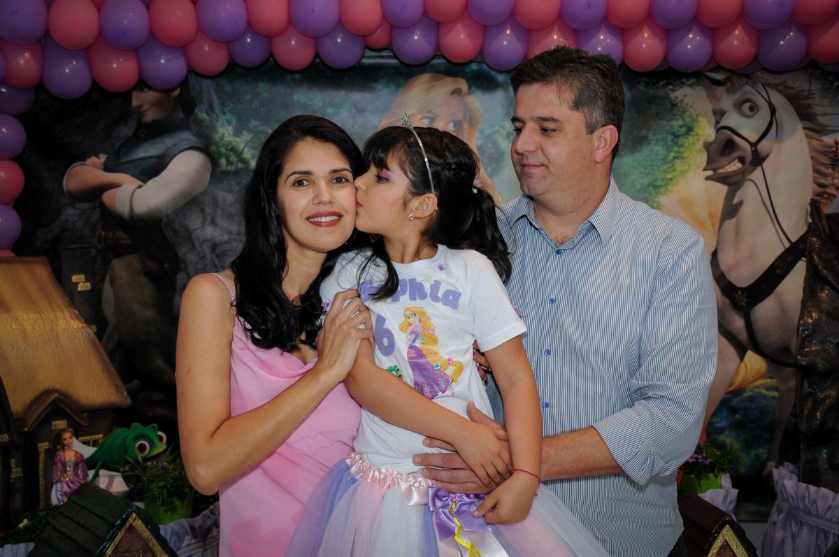 beijinho da aniversariante em sua mãe em frente a mesa tema rapunzel no Buffet Fábrica da Alegria Osasco, São Paulo
