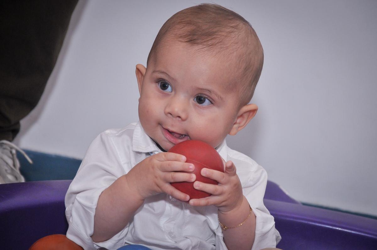 com uma bolinha na mão Matheus brinca em sua festa de batizado no festa no condomínio
