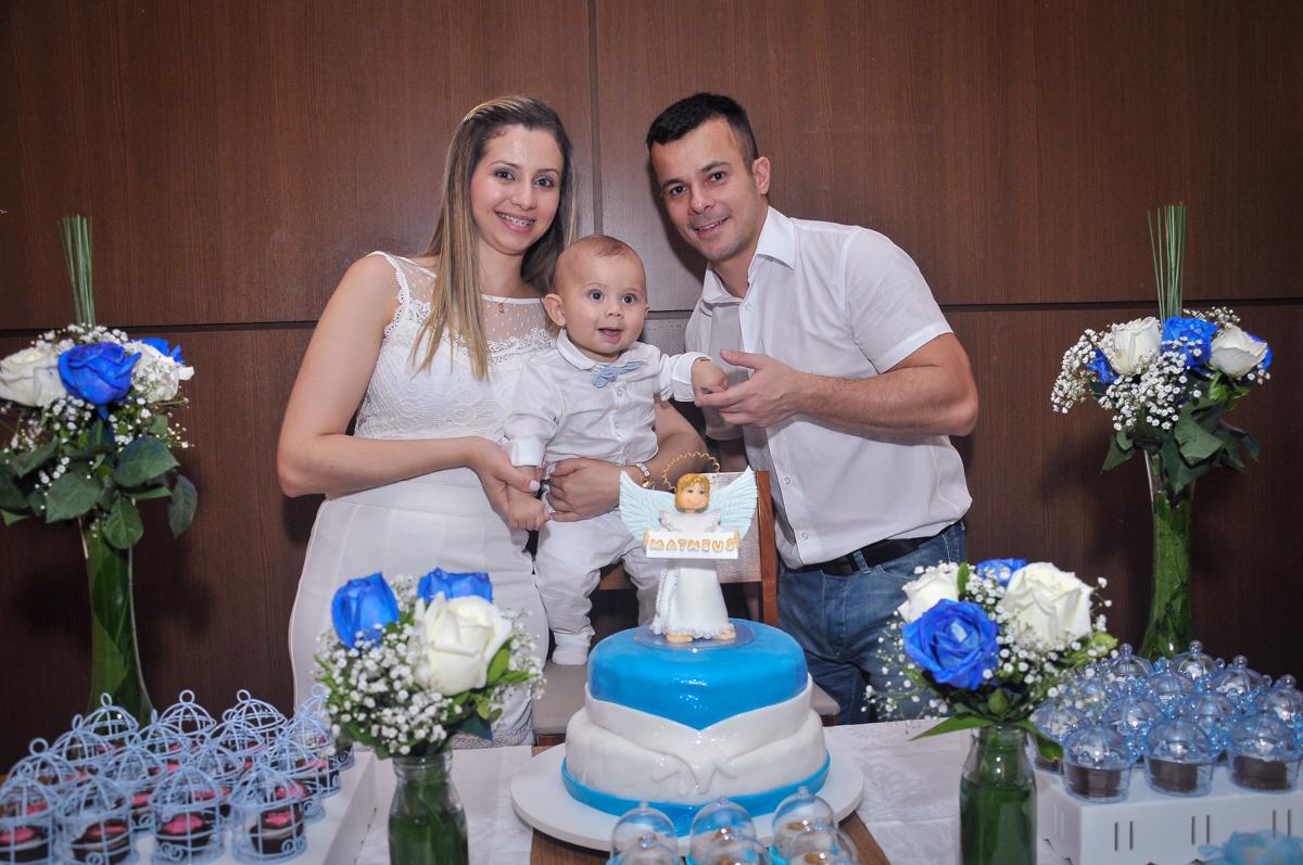 Matheus e seus pais na mesa decorada para a festa de batizado festa no condomínio
