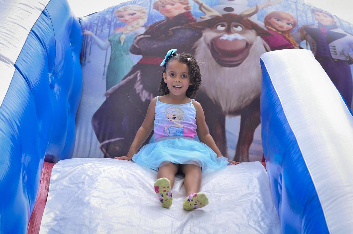 letícia se diverte no escorregador inflável no Condomínio São Paulo, SP, tema da festa Frozen