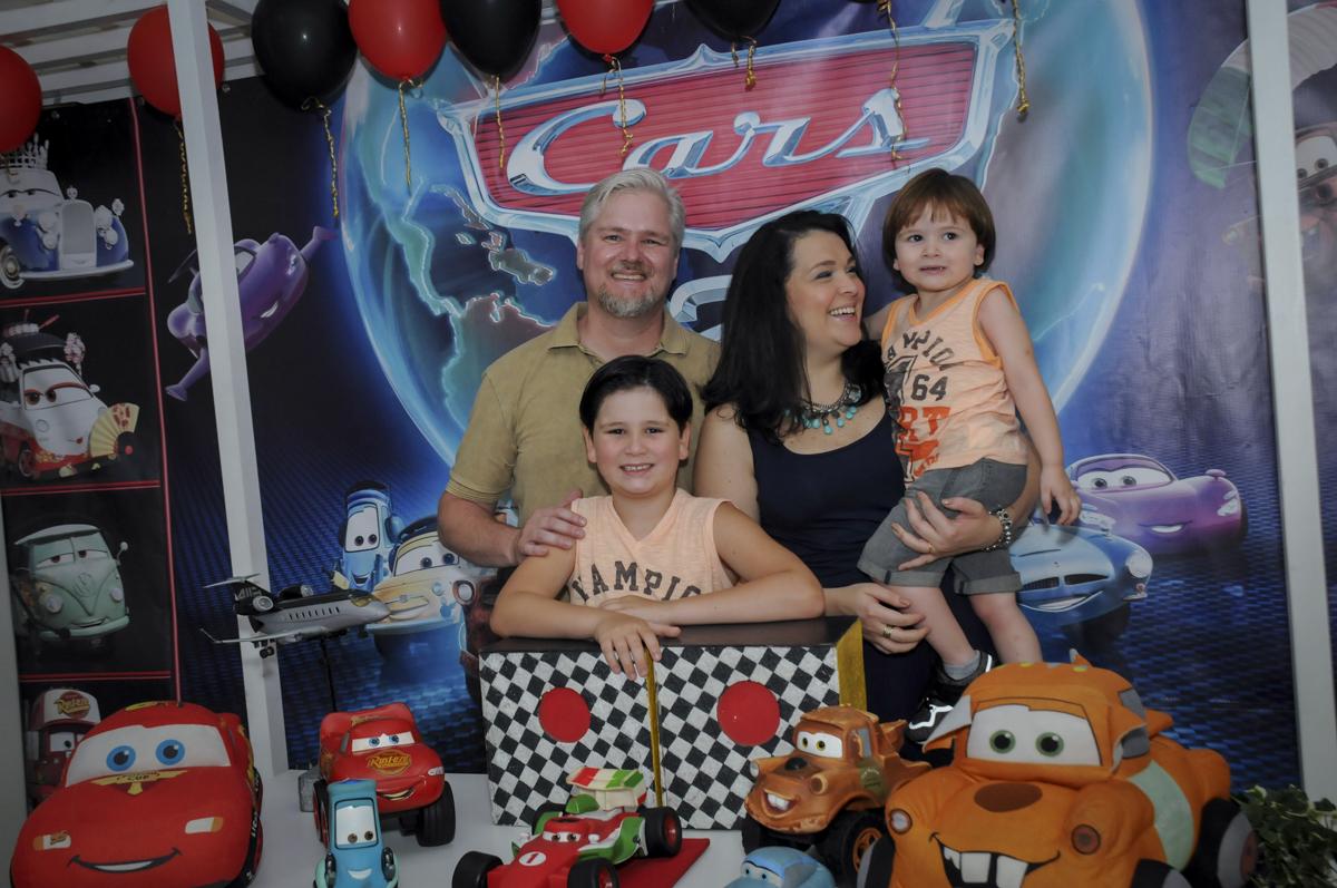 foto da família na mesa decorada no  buffet feliz da vida, festa infantil Théo 3 aninhos, tema da festa carros