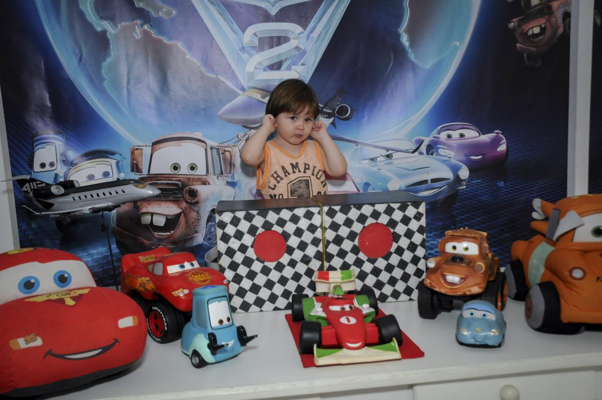 aniversariante sendo fotografado na mesa decorada no  buffet feliz da vida, festa infantil Théo 3 aninhos, tema da festa carros
