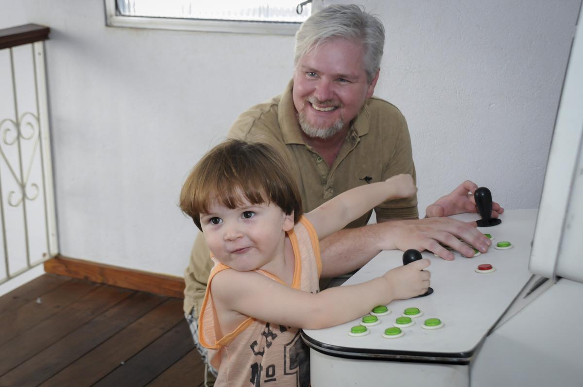 pai e filho brincam no game no  buffet feliz da vida, festa infantil Théo 3 aninhos, tema da festa carros