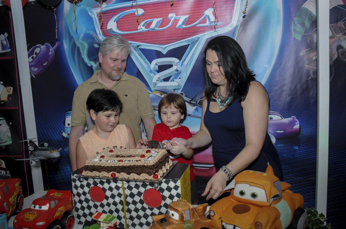 cortando o primeiro pedaço de bolo no  buffet feliz da vida, festa infantil Théo 3 aninhos, tema da festa carros