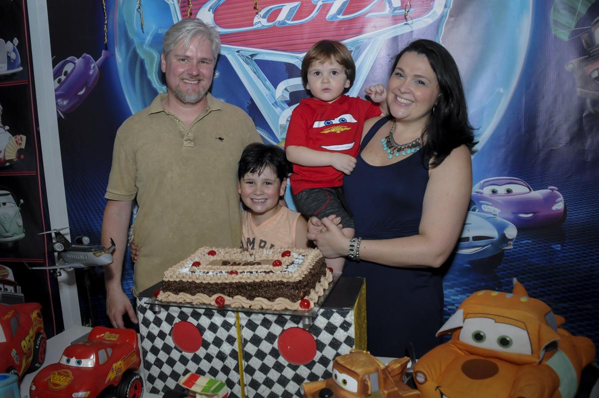 foto da família na mesa do bolo no  buffet feliz da vida, festa infantil Théo 3 aninhos, tema da festa carros