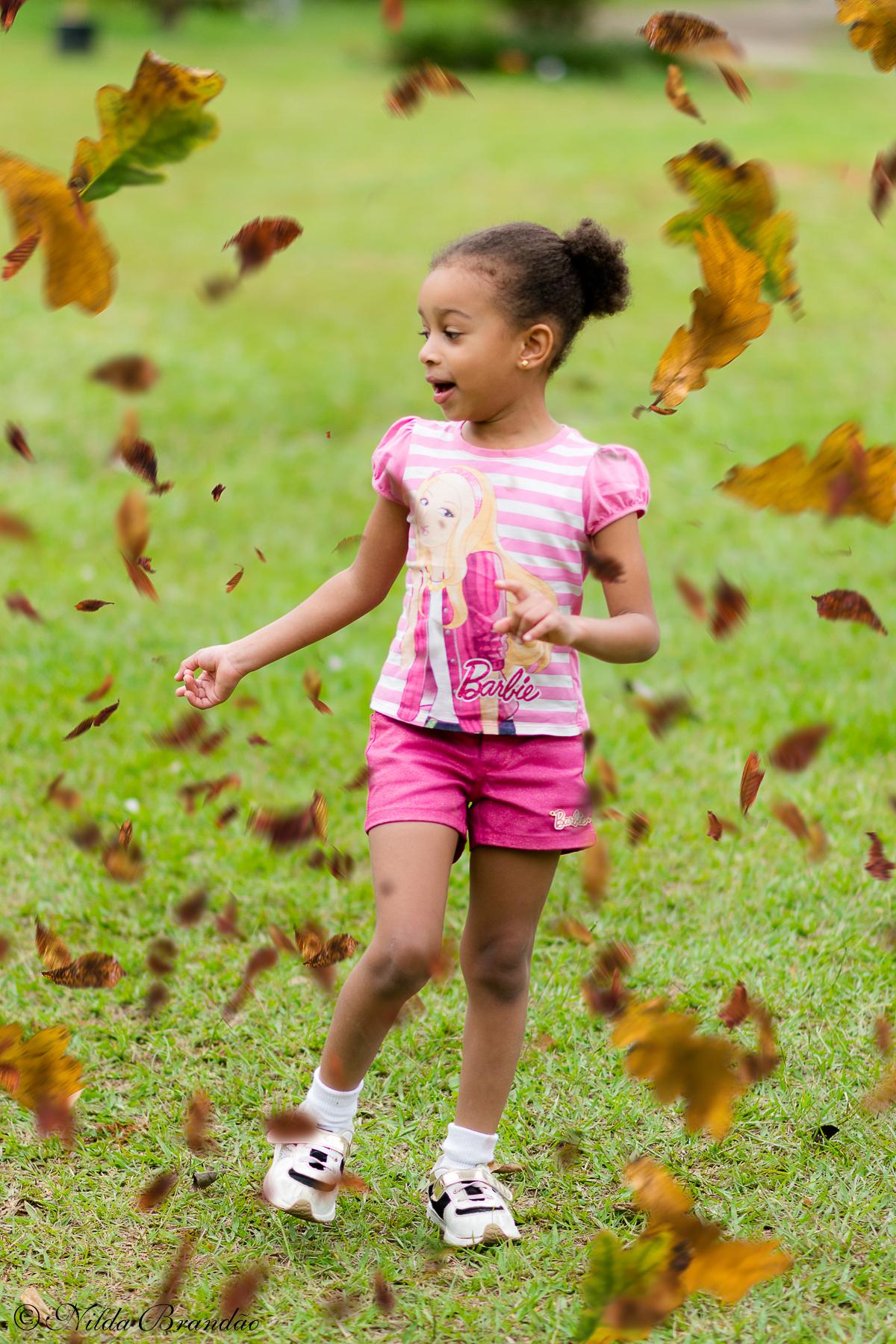 Chuva de folhas é comum no outono, a Julia se divertiu com elas no seu ensaio infantil.
