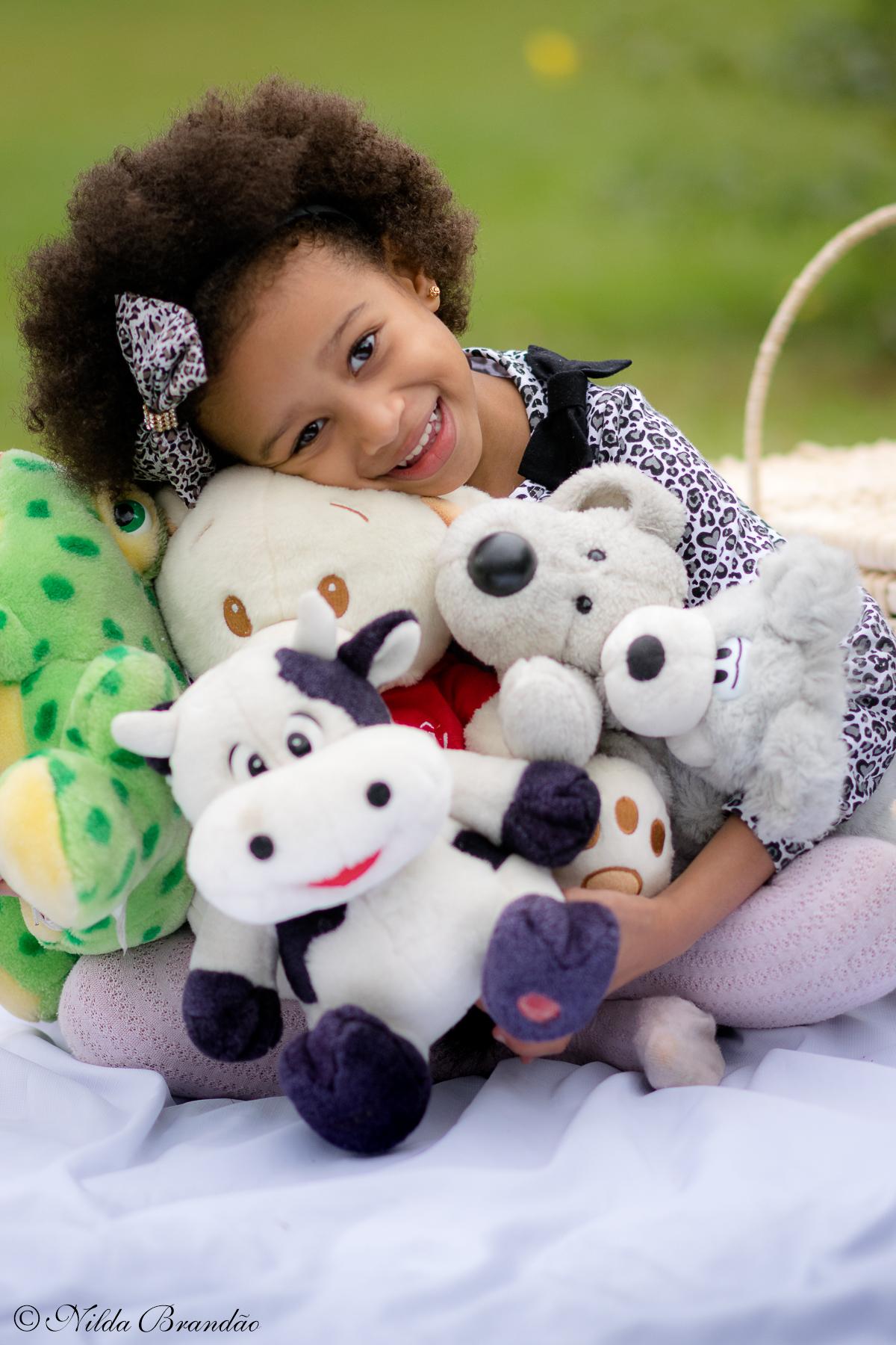 Julia posa com seus bichinhos favoritos. Ensaio infantil da Julia, no parque em São Paulo.