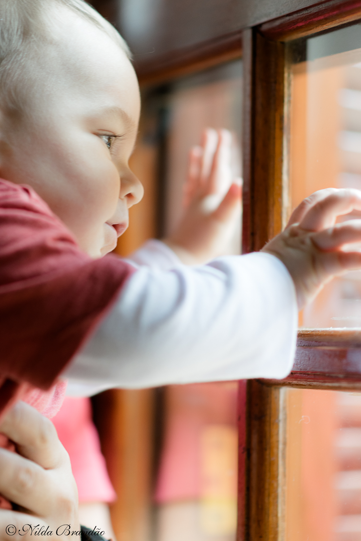 Olhando pela janela Fazer fotografias acompanhando mensalmente o crescimento do bebê é uma forma linda de recordação do primeiro ano de vida.