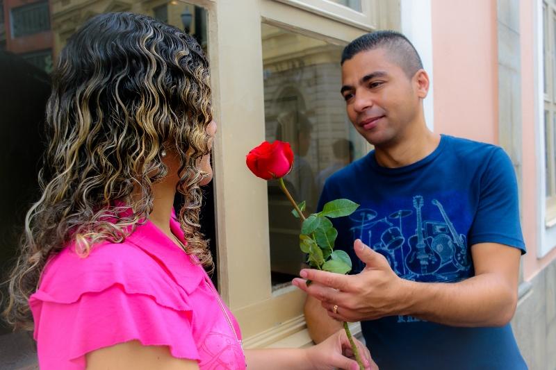 Homem oferece roa vermelha para a mulher