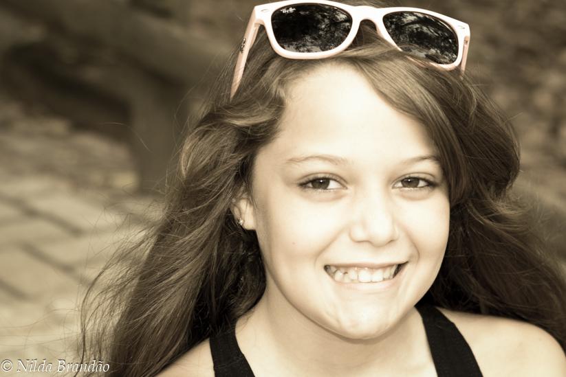Menina de cabelo colto sorrindo usando óculos de sol