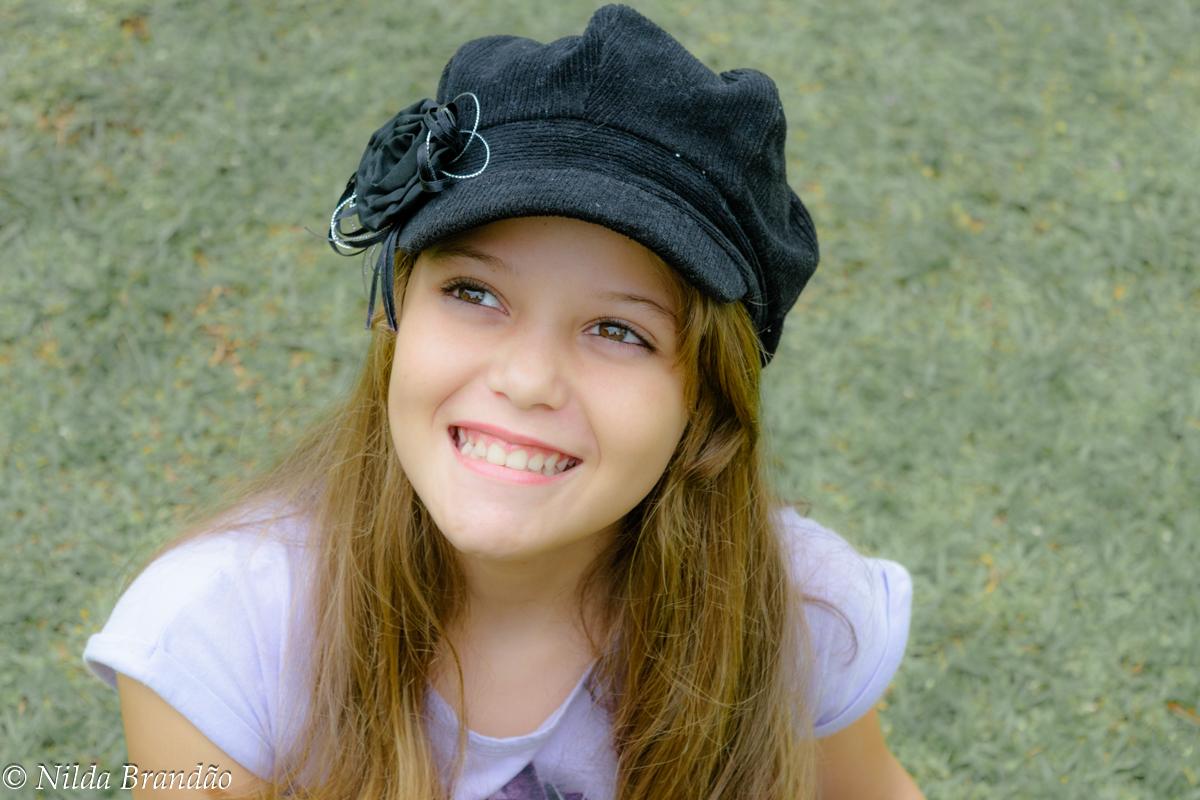 Menina sorringo usando boina preta