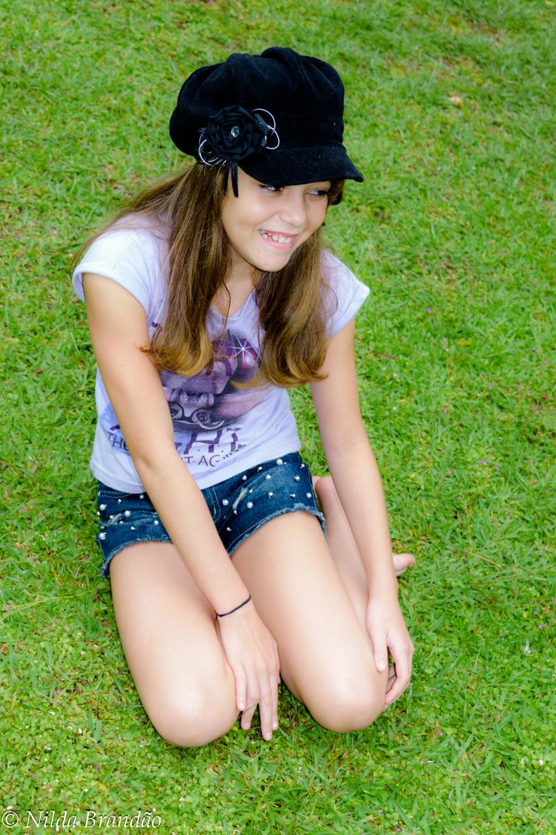 Menina sentada na grama, usando short jeans e camiseta