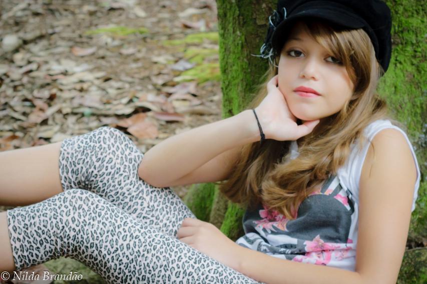 Menina sentada em tronco de árvore