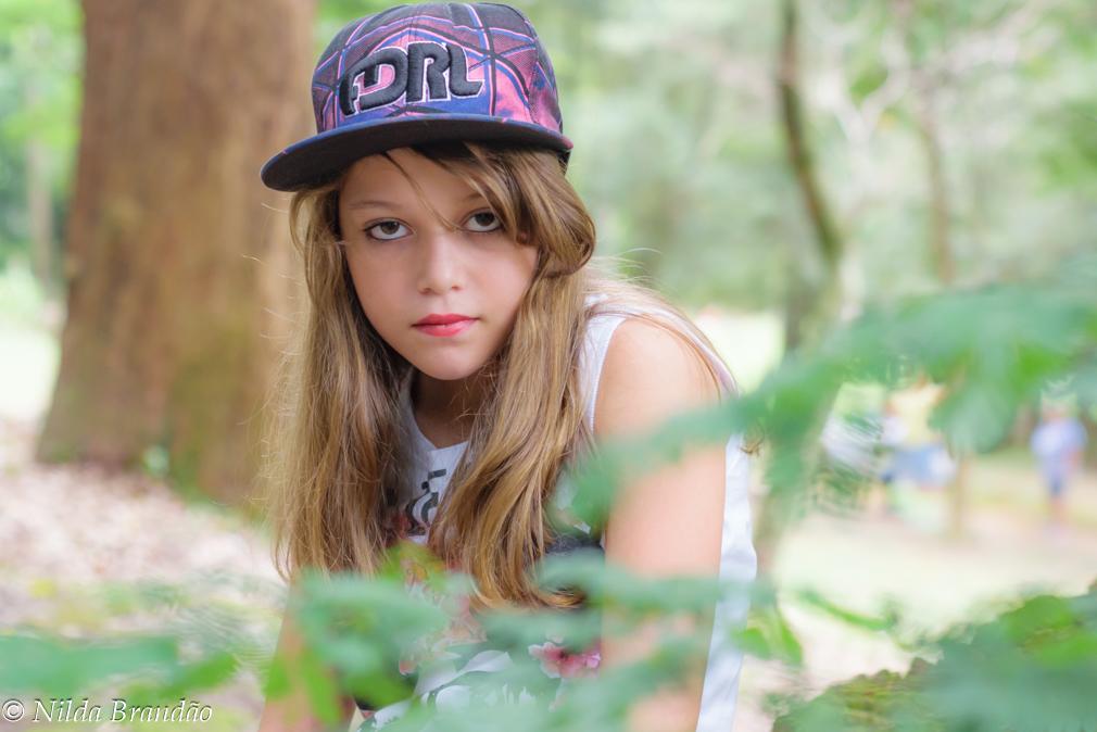 Retrato de menina com folhas desfocadas em primeiro plano
