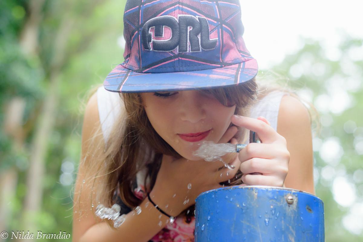 Menina bebendo agua em fonte no parque