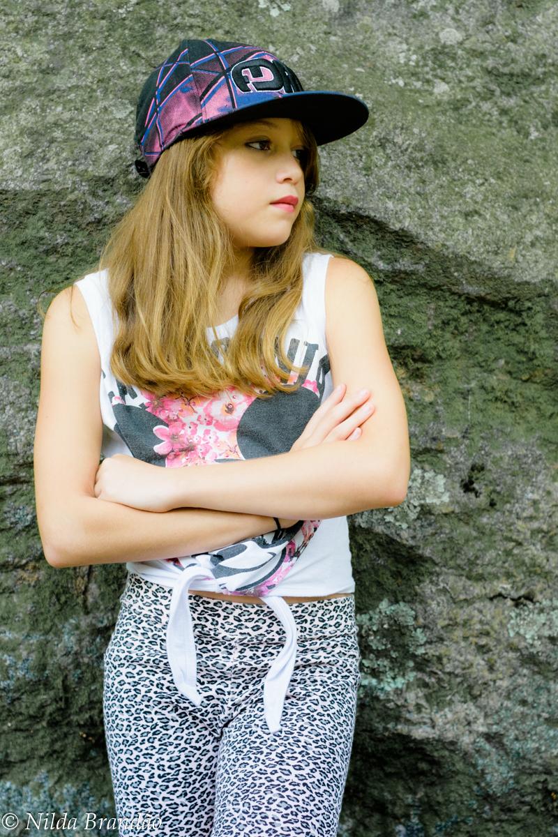 Menina usando boné encostada em parede de pedra