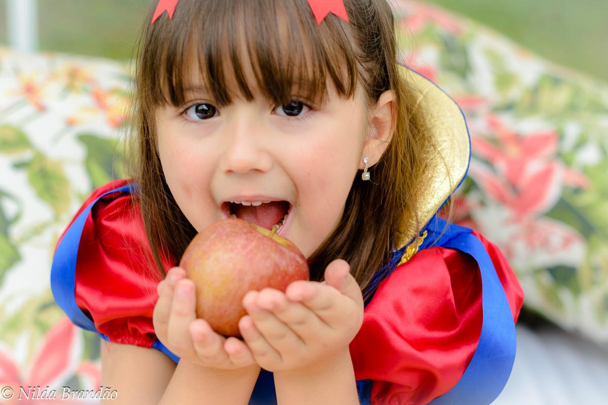 Menina com fantasia de branca de neve dando primeira mordida na maçã