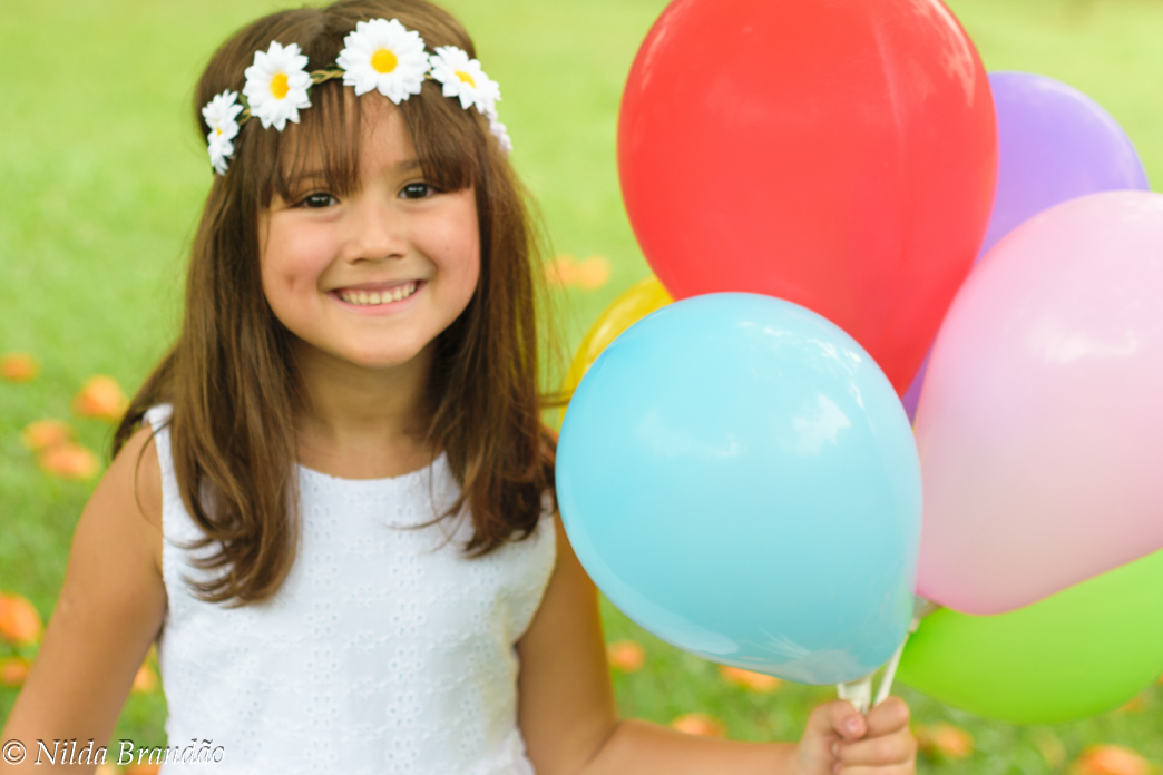 Menina segurando balões coloridos