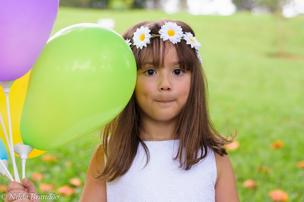 Menina com tiara de flores segurando balões