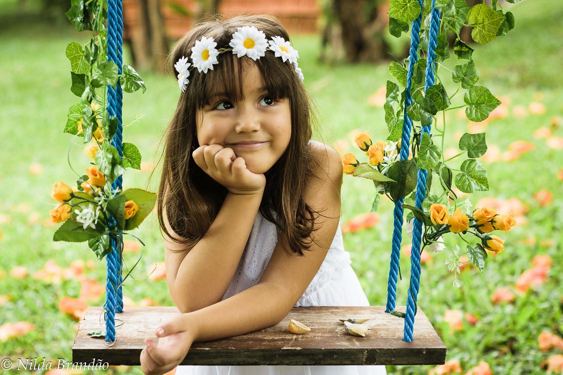 Menina com tiara de flores em balanço