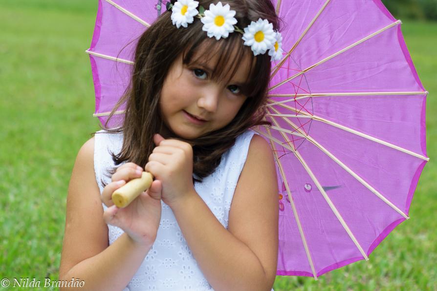 Menina posa para foto, segurando sombinha japonesa