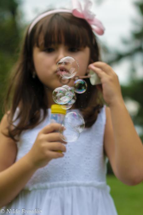 Menina fazendo bolinha de sabão