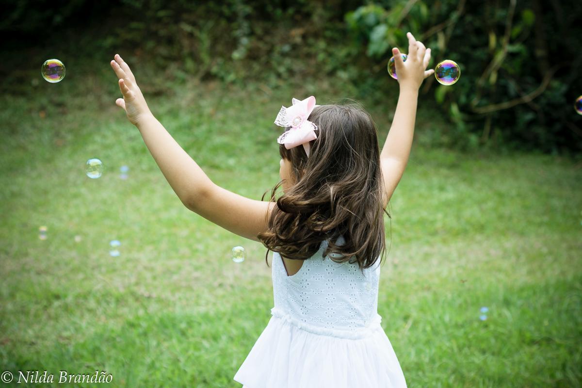 Menina brinca perseguindo bolhas de sabão
