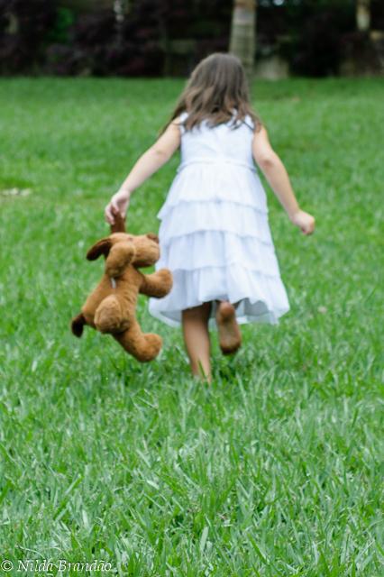 Correndo no campo com seu inseparável ursinho de pelucia.
