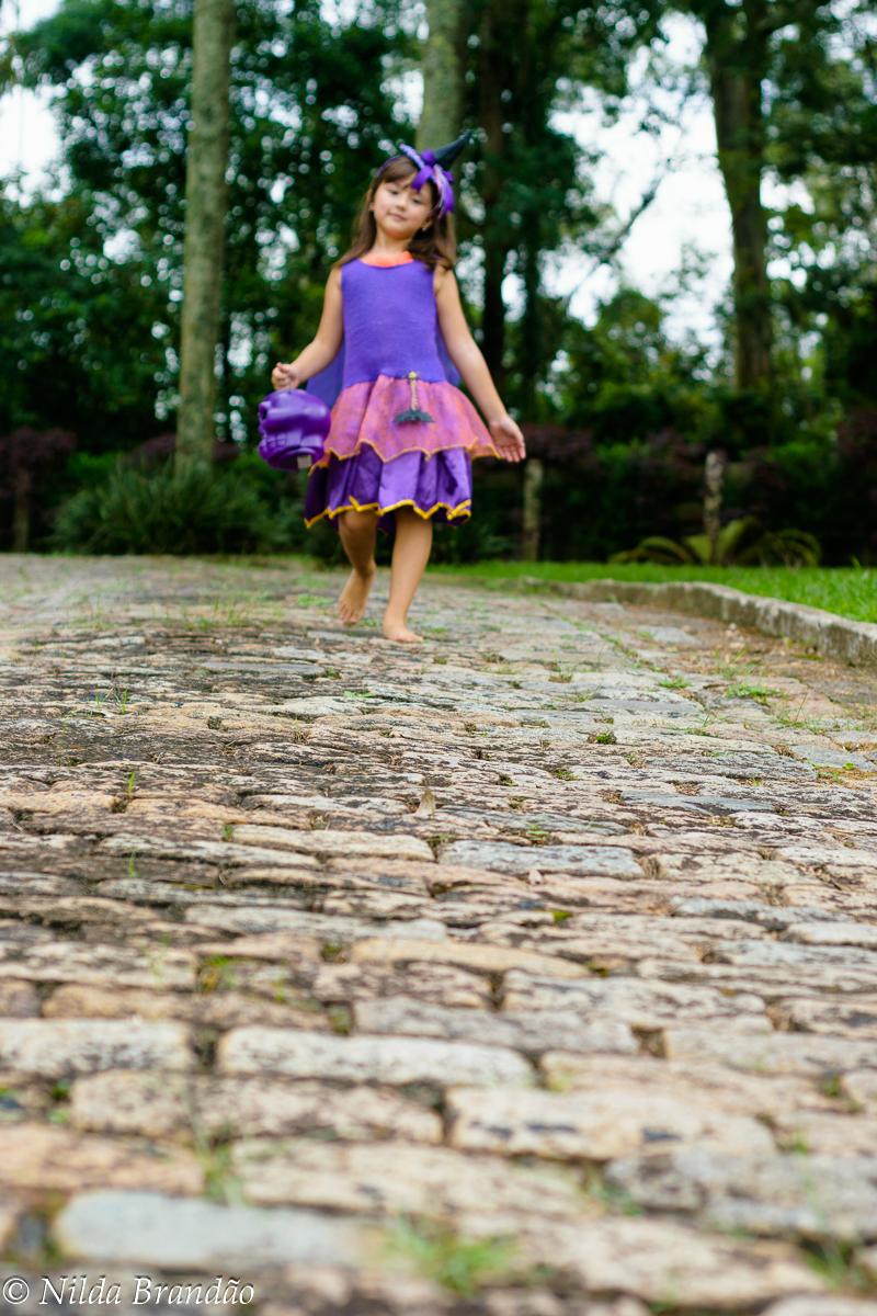 Lá vem a bruxinha! menina caminhando em estrada de pedra
