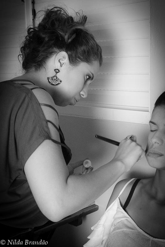 Maquiadora prepara a modelo para sessão de fotos num abela foto em preto e branco.