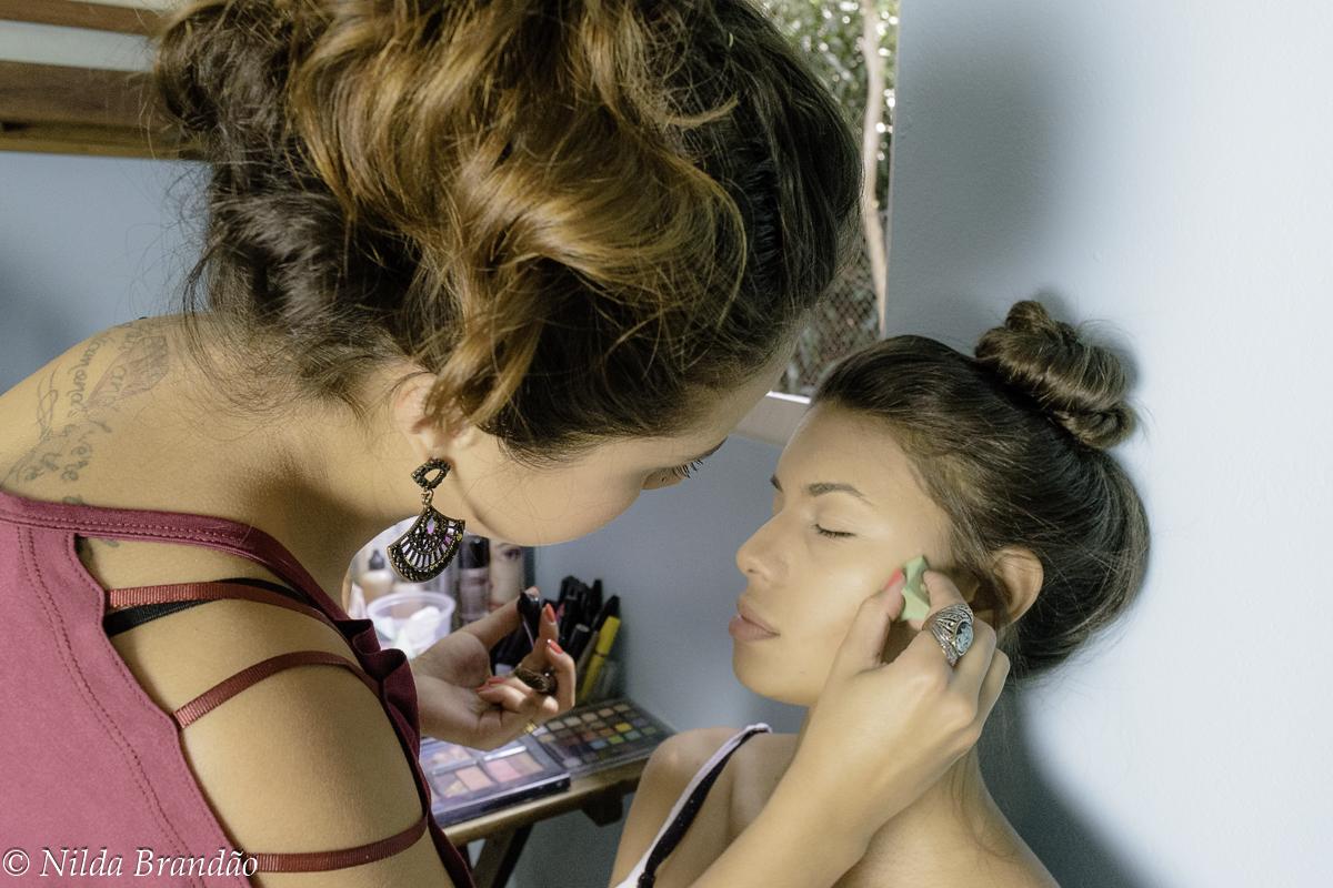 Modelo fecha os olhos enquando maquiadora trabalha em seu rosto