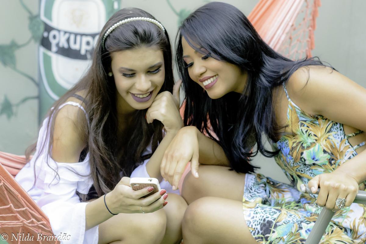 Amigas olham celular em momento de descontração no ensaio fotografico