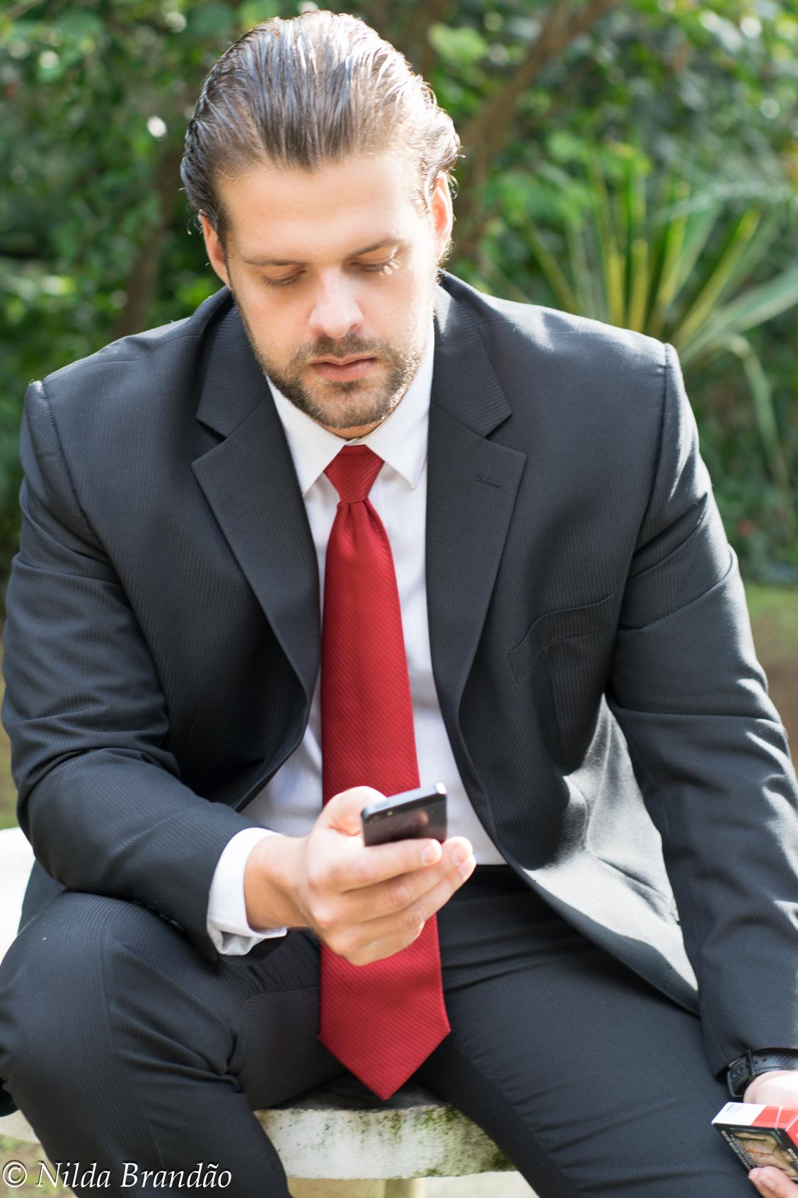 Ele está um charme nesse terno, a gravata vermelha deu um toque especial, mas o olhar não sai da tela do celular, checando os compromissos.