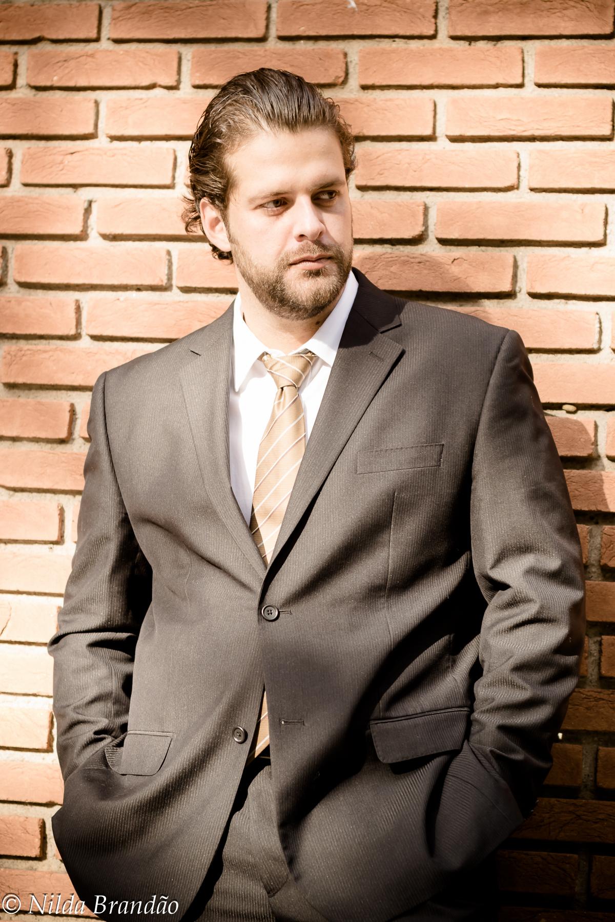 Homem em ensaio fotográfico, usando terno no fundo de parede de tijolos