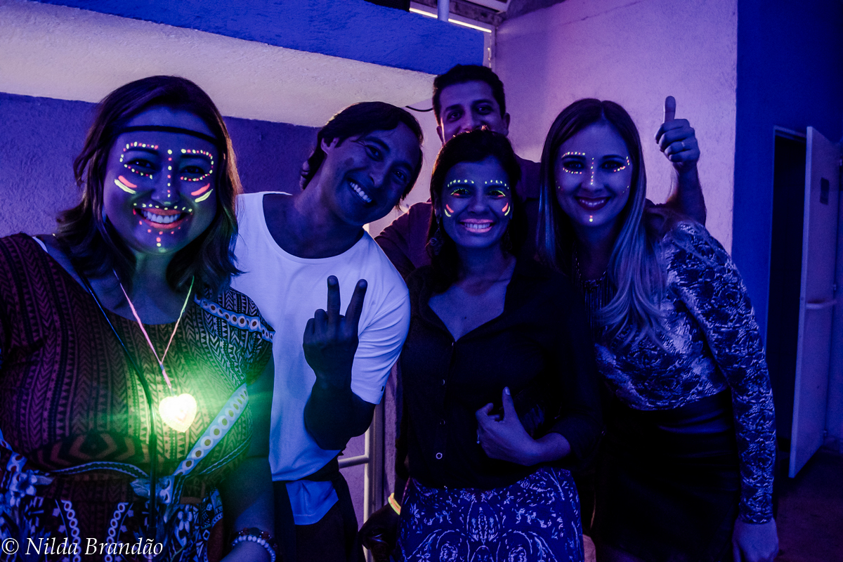 Amigos posam para fotos com luz de neon