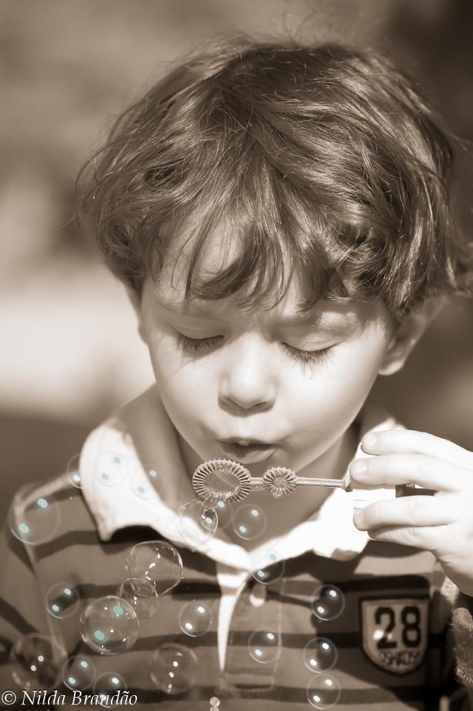 Foto em preto e branco de menino fazendo bolas de sabão