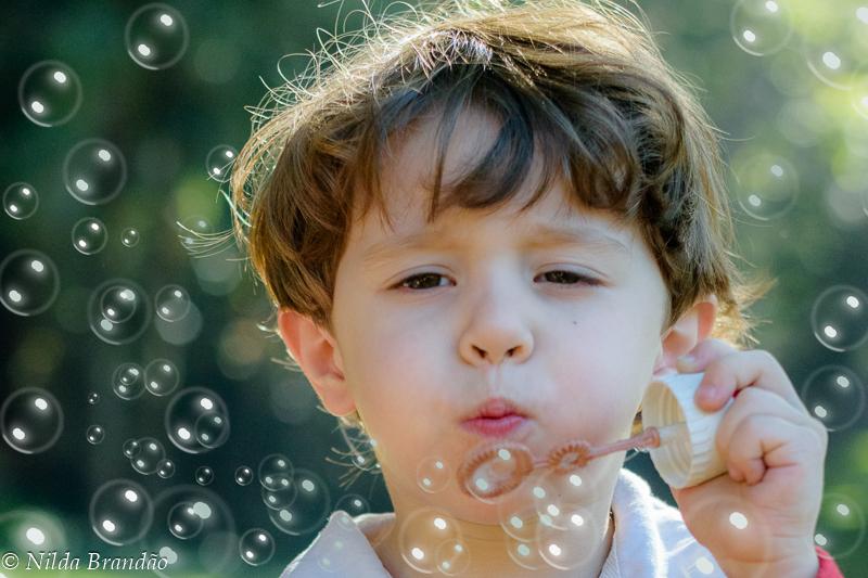 Menino brincando de fazer bolhas de sabão