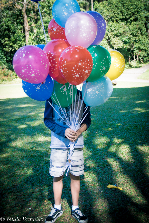 Adolescente se escondendo atras de coloridos balões de gas helio
