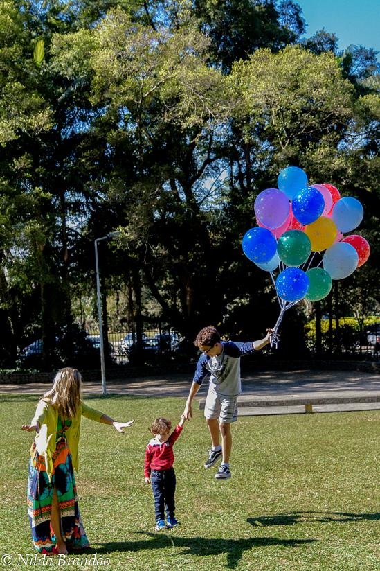 Familia no paque brincando com balões de gas helio