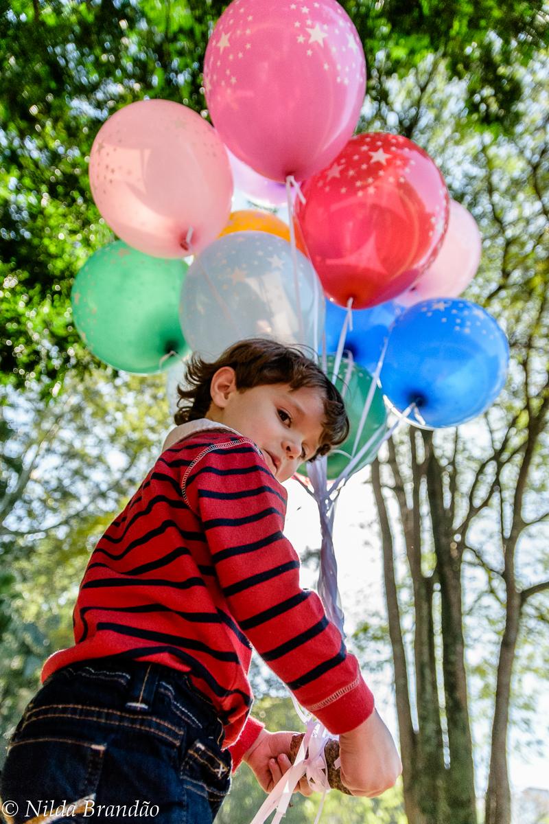 Criança no parque com balões de gas helio