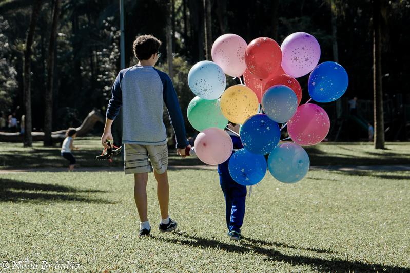 Irmãos passeando no parque com bolas de gás helio