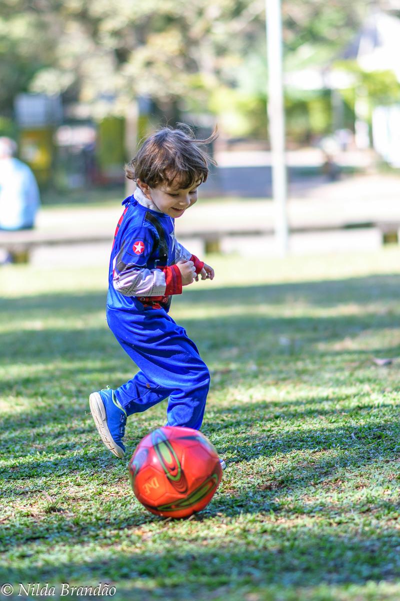 Menino jogando bola no parque