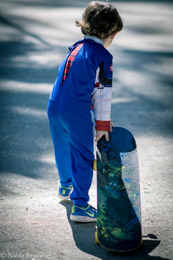 Menino carregando o skate no parque
