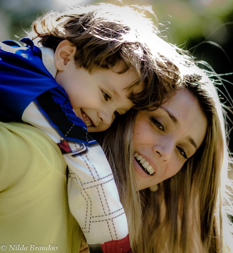 mãe sorrindo ao levar o filho de cavalhino