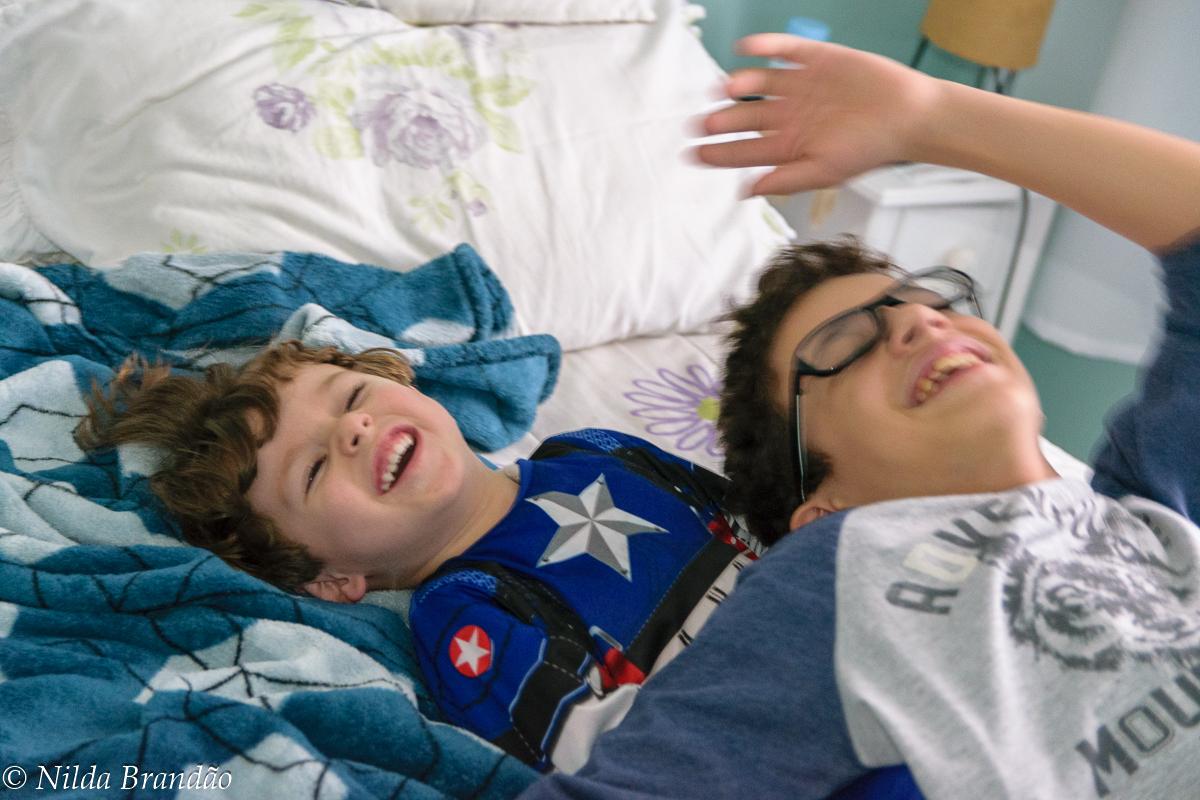Brincadeira de irmãos em guerra de travesseiro.