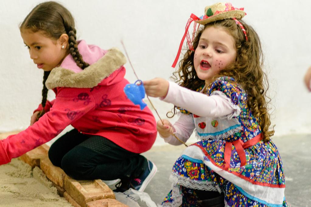 Crianças brincando de pescaria na festa junina