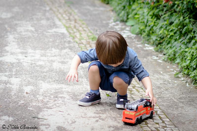 Menino brinca com seu carrinho de bombeiro