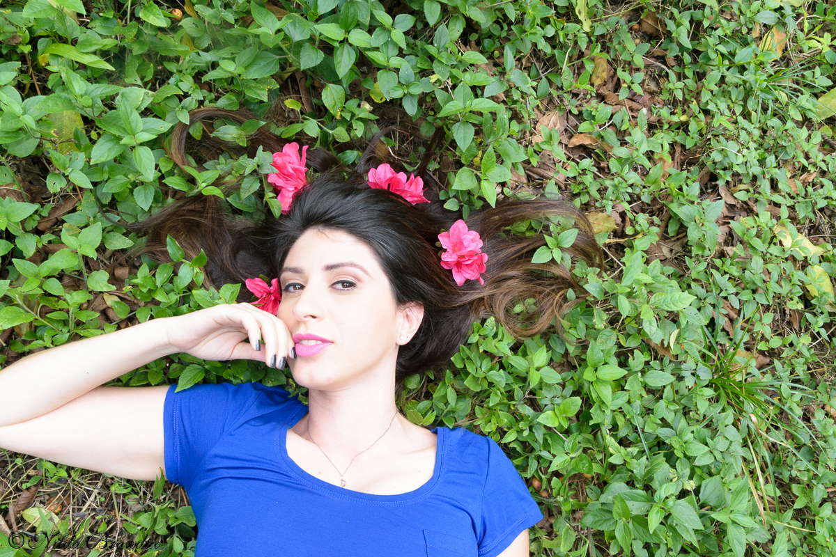 Deitada na grama e com cabelos enfeitados de flores no parque Burle Marx em São Paulo