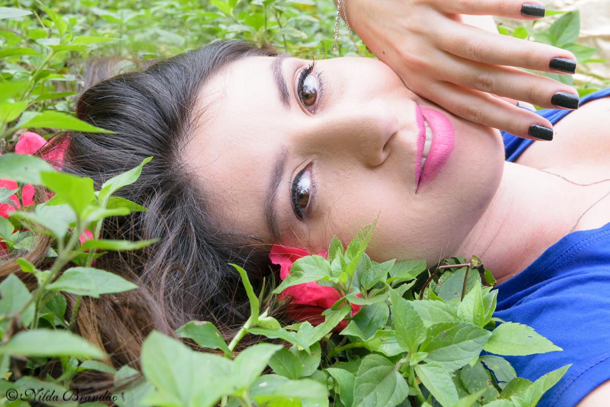 Deitada na grama e enfeitada de flores, para ensaio fotografico feminino em São paulo